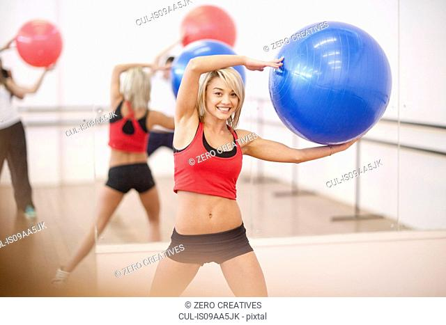 Young woman holding exercise ball in aerobics class