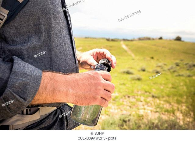Cropped close up of male hikers hand holding water bottle, Cody, Wyoming, USA