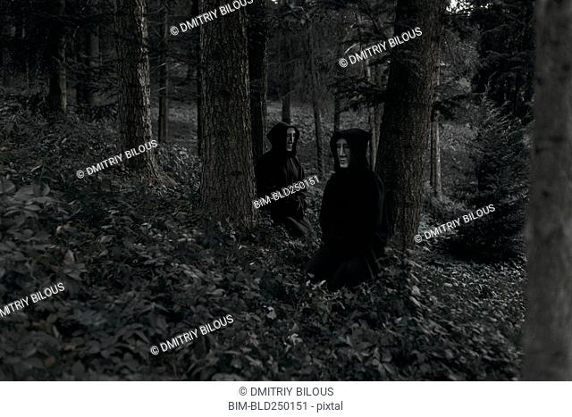 People wearing black robes and white masks sitting in forest