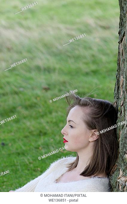 Serious young woman leaning against a tree looking away