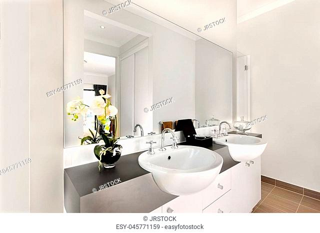 Luxurious washroom included two shiny white washstand made of ceramic, there are silver and curved faucet fixed to sink. The taps can give warm water
