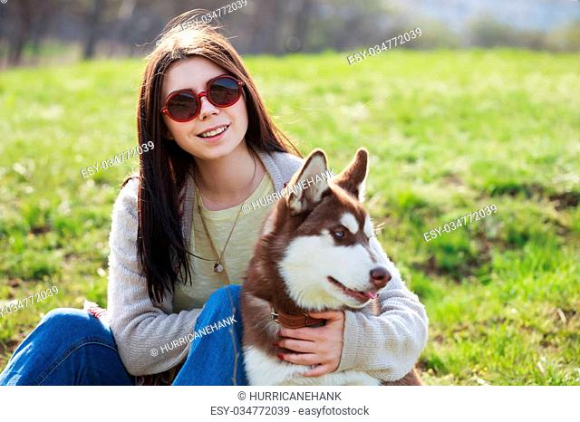 Smiling young brunette girl sitting with her husky dog in green park outdoors. Cute and friendly couple enjoying the nature