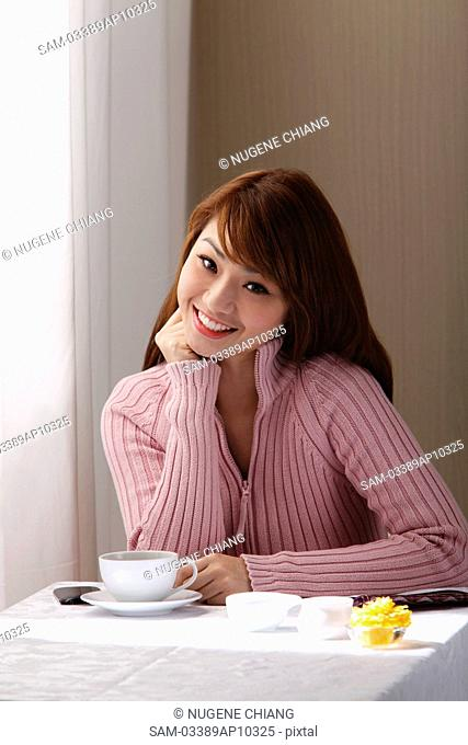 Young woman sitting in cafe near window