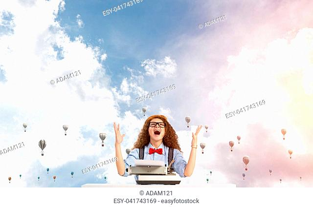 Young and beautiful woman writer in hat and eyeglasses using typing machine while sitting at the table with flying aerostats and cloudy skyscape on background