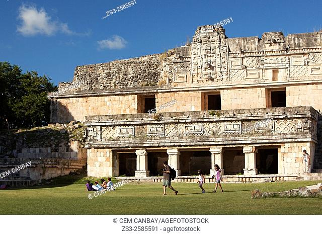 Tourists walking around the Quadrangle Of The Nuns in Uxmal ruins, Prehispanic Mayan city of Uxmal Archaeological Site, Yucatan Province, Mexico