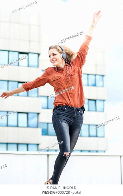 Dancing woman with arms outstretched listening music with headphones