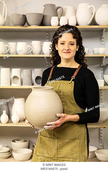 Woman with curly brown hair wearing apron holding unfired spherical clay vase