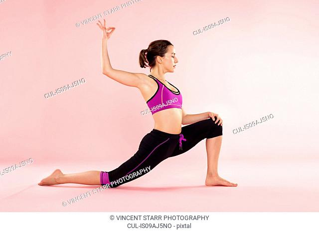 Studio shot of young woman in yoga position with legs outstretched and arm raised