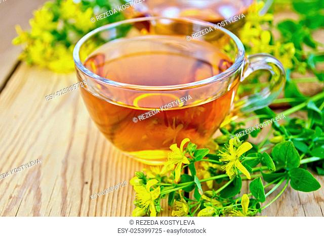 Herbal tea in a glass cup and teapot, fresh flowers tutsan on the background of wooden boards