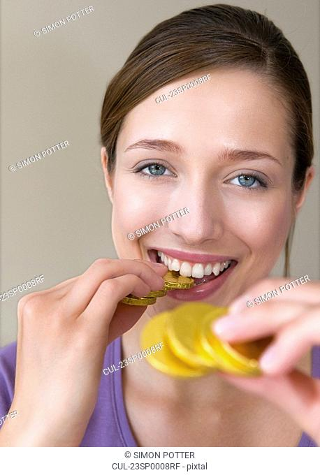 Woman bites on gold coins