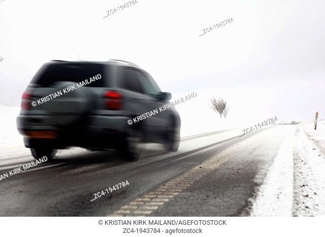 Fast car on snowy winter road