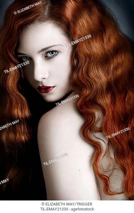 A glamorous portrait of a young adult with wavy red hair looking over her shoulder