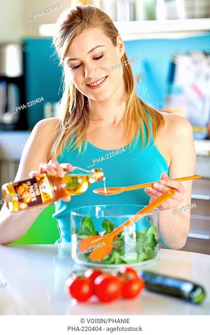 Woman adding walnut oil on a salad