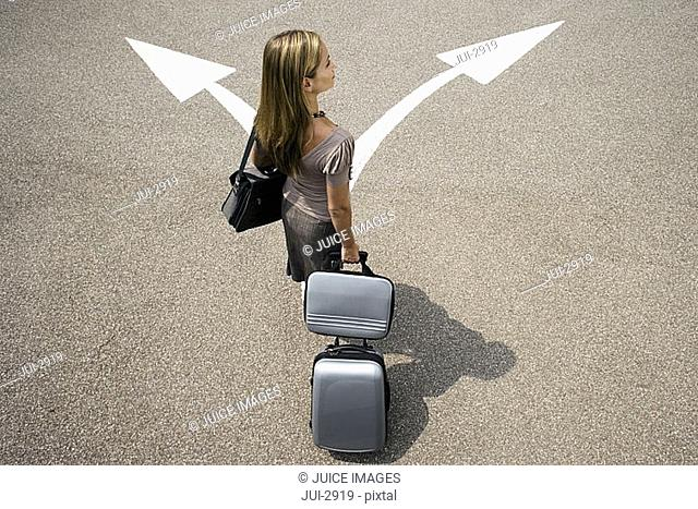 Businesswoman standing with luggage in car park near opposing arrow signs, rear view, elevated view