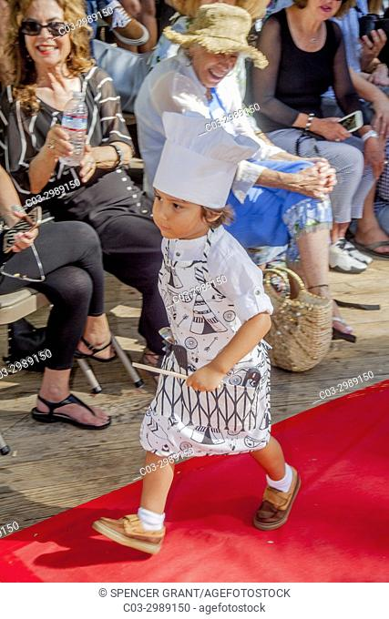 A Hispanic 3-year-old boy models a stylized chef's outfit in an outdoor fashion exhibition in Laguna Beach, CA. Note red carpet