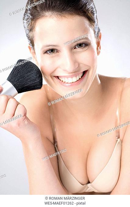 Young woman using make-up brush, close up