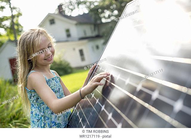 A young girl beside a large solar panel in a farmhouse garden