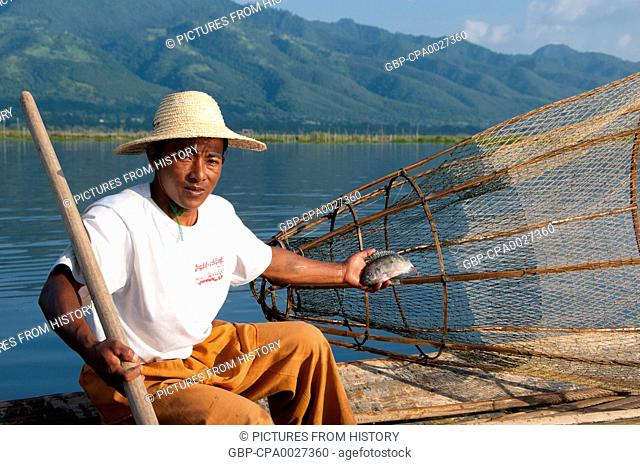 Burma / Myanmar: A leg rowing Intha fisherman shows off his skills with a large conical fish trap at Inle Lake, Shan State