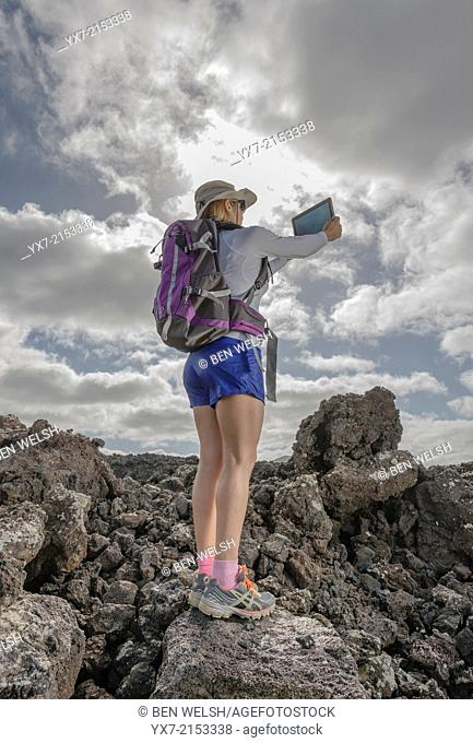Tourist using a Tablet at Timanfaya National Park, Lanzarote, Canary Islands, Spain