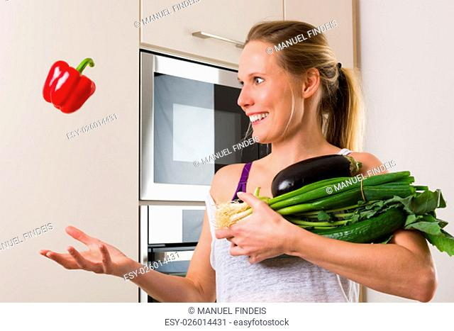 Sporty, Caucasian woman juggling vegetables for healthy eating in the kitchen