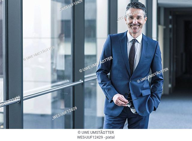 Portrait of smiling businessman on office floor