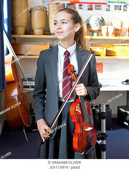 Proud high school student with violin in music classroom