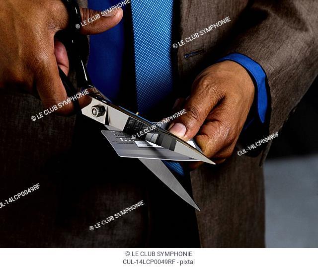 Business man credit card in half