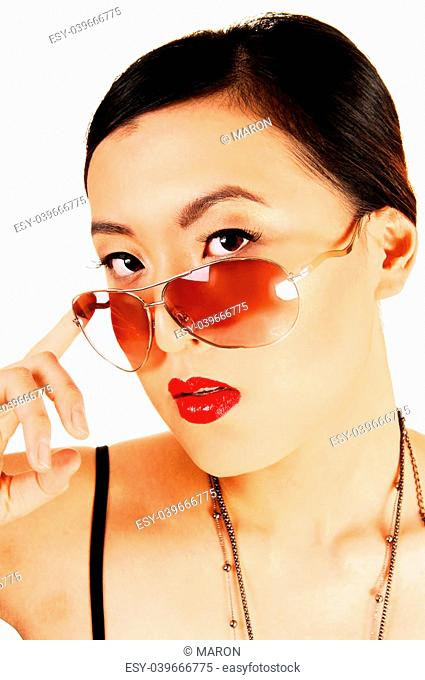 A closeup shoot of a classy young chinese woman looking over her sunglasses for white background