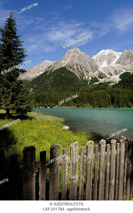 Wooden fence in front of the Antholzer lake in idyllic mountain scenery in the sunlight, Val Pusteria, South Tyrol, Italy, Europe