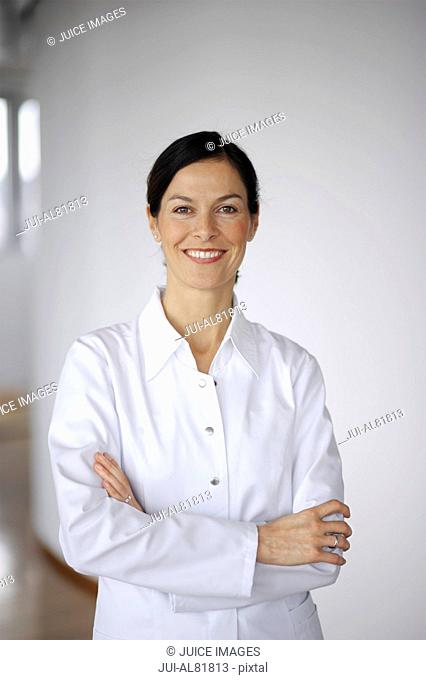 Woman smiling with arms crossed indoors