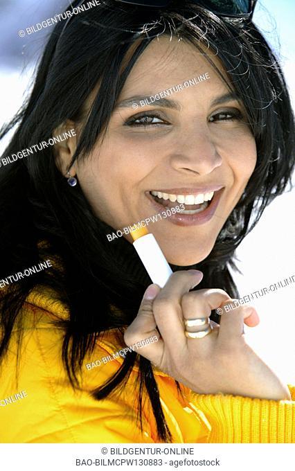 winter holiday woman putting sun cream on her lips