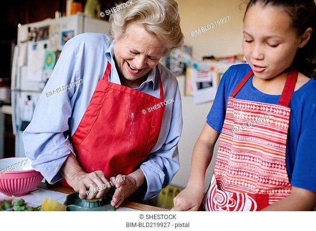 Grandmother and granddaughter squeezing juice in kitchen