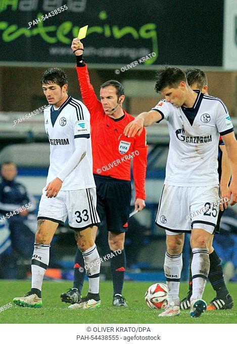 Schalke's Roman Neustaedter (L)receives a yellow card from referee Marco Fritz (C) while Schalke's Klaas-Jan Huntelaar walks away during the Bundesliga soccer...