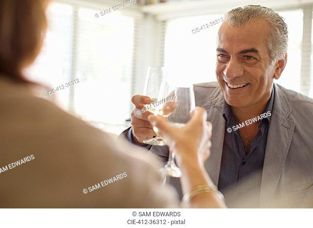 Smiling senior man drinking wine, toasting wine glasses with woman at restaurant