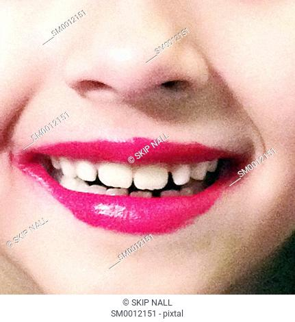 Closeup of a little girl's lips with messy lipstick