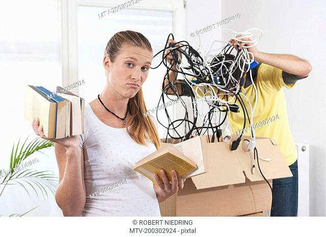 Confused pregnant woman packing with her husband while moving to new apartment, Bavaria, Germany