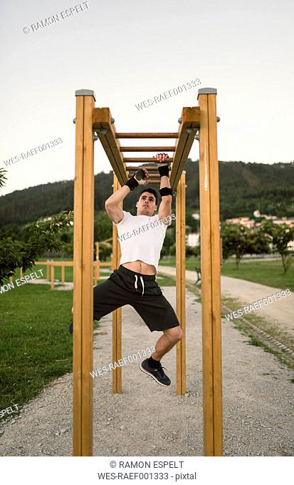 Athlete man, training on climbing frame, outdoor