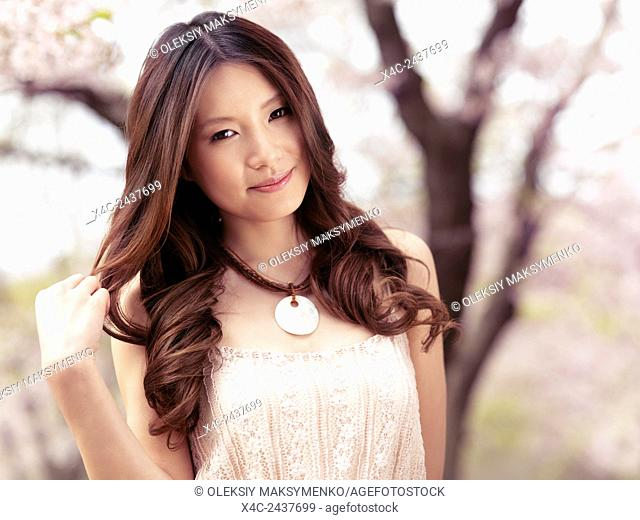Beauty portrait of a young asian woman with long brown hair in park with cherry blossom in spring