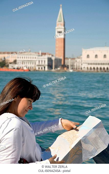 Young woman reading map on waterfront opposite St Marks Square, Venice, Italy