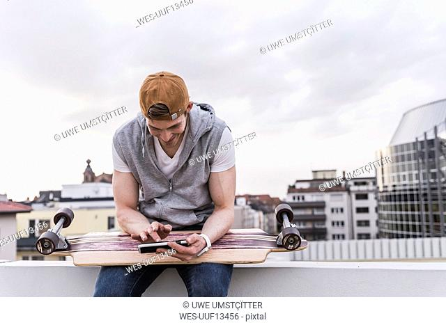 Smiling man sitting in the city with skateboard using cell phone