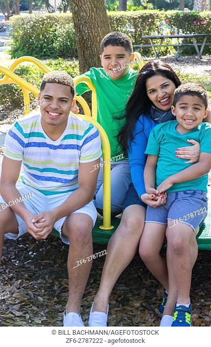 Hispanic family at playground on merry go round portrait smiling Mom and sons Model Released, MR-8, MR-9, MR-10, MR-11