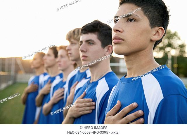Soccer players with hands on their hearts