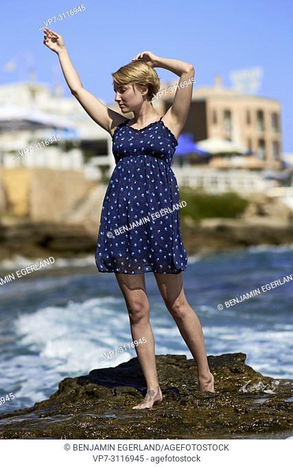 woman at beach, sensual, enjoying warm summer breeze, in holiday destination Chersonissos, Crete, Greece