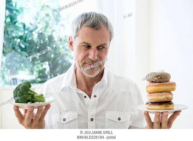 Older Caucasian man choosing between broccoli and donuts