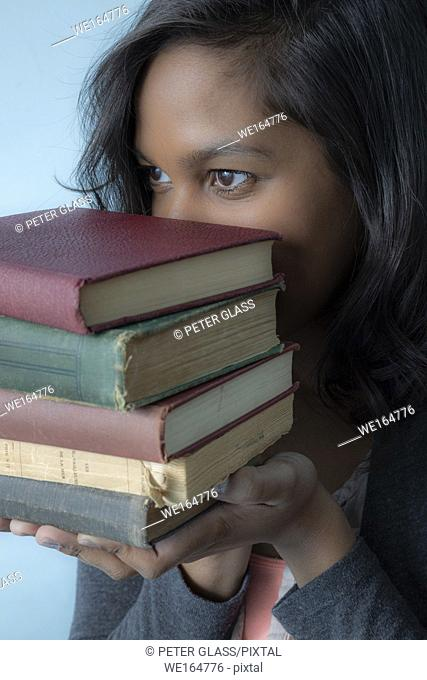Young Hispanic woman holding a pile of books