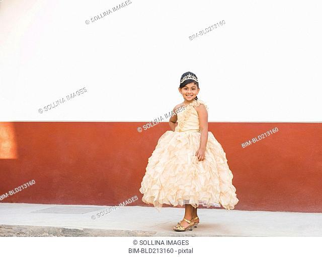 Hispanic girl posing in ornate gown and tiara
