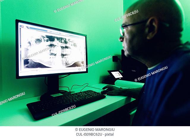 Dentist looking at dental x-ray on computer