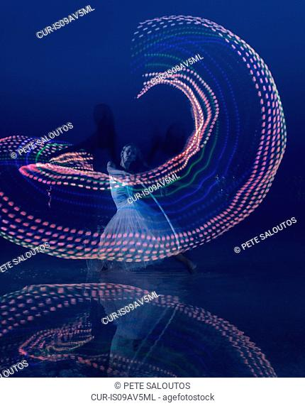 Woman dancing with illuminated multi-coloured hoop at dusk