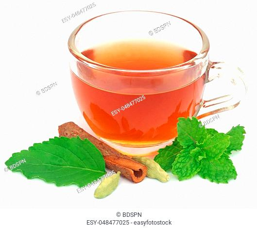 Herbal tea in a cup with different herbs over white background