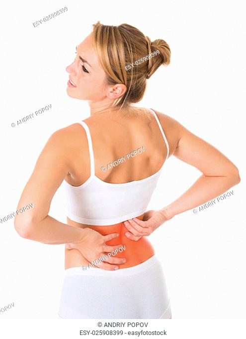 Sad young woman suffering from back pain over white background